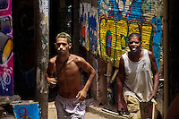 Brazilian men walk in front of the wall covered by graffiti in Rocinha, the largest slum in Rio de Janeiro, 28 February 2004.