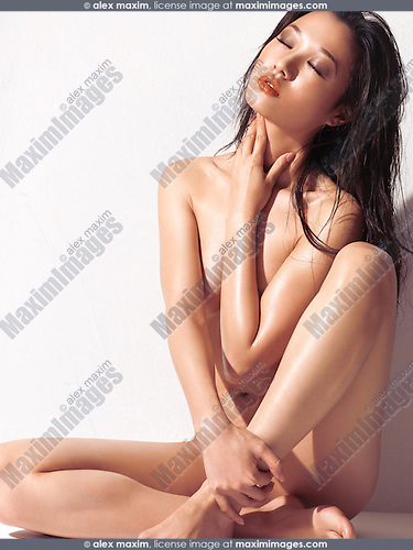 Beautiful young asian woman with bare body and shiny skin sitting in front of a white wall in bright sunlight