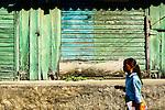 Dominican girl walks on side street in Puerto Plata, Dominican Republic
