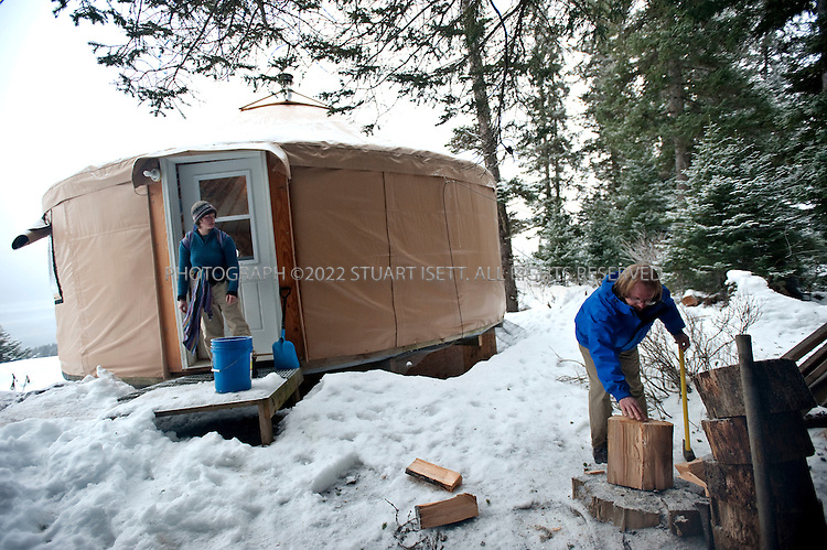 12/11/2009--Seldovia, Alaska, USA..Bretwood Higman (right), chops wood used to heat the yurt in Seldovia, Alaska while his wife Erin McKittrick looks on...The yurt is made by Nomad Shelter in Homer, Alaska, and cost about $14,000.  Bretwood Higman ('Hig'), 33 and Erin McKittrick, 30, built it in November, 2008 on land owned by Hig's mother in Seldovia. The yurt is 24' in diameter, the ceiling is over 12' in the middle, 7' around the edge. It has no running water but does have electricity and internet access...McKittrick grew up in Seattle and met Higman, from Seldovia, at Carleton College in 2001.  In June 2007, the couple left Seattle for the Aleutian Islands, traveling 4000 miles solely by human power through some of the most rugged terrain in the world; their adventure has recently been published in a book written by McKittrick with Hig's photographs titled, 'A Long Trek Home: 4,000 Miles by Boot, Raft, and Ski'...Together, the couple also run a small environmental non-profit, Ground Truth Trekking, which uses trekking to explore the complexities of natural resource issues.  The couple lives with their 10 month old son son, Katmai, in Seldovia, Alaska, a 300 person village just off the end of the road system...©2009 Stuart Isett. All rights reserved.