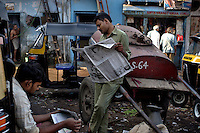 Auto rickshaw wallahs reads papers in the early morn in Dharavi.