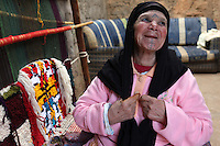 Khina Boujnoui is photographed next to a communal loom in Tamda, Morocco. Boujnoui is part of a traditional Berber family that has been weaving for generations.