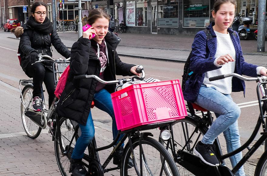 Nederland, Utrecht, 26 maart 2015<br /> Fietsers op straat. Jonge meisjes met telefoon aan het oor in verkeer<br /> <br /> Foto: (c) Michiel Wijnbergh