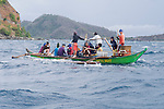 Anilao, Philippines; fourteen fishermen in a green, motorized Banca, or outrigger boat, using nets to catch fish above the reef at Sombrero Island