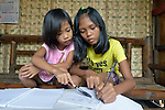 Necabless Barrio (right), is a 12-year old girl on Bayas, a small island in the Philippines municipality of Estancia, in Iloilo Province. Here she does her homework with help from her sister Ziria. <br /> <br /> The island was ravaged by the passage of Typhoon Haiyan, known locally as Yolanda, in November 2013. Both deaf and mute, Barrio fled with her family as the waters rose, but got her foot tangled in some electrical cables. With the water at the girl's neck and still rising, her mother managed to free her and get her to higher ground.