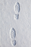 Footprints in the snow in frosty wintry landscape in The Cotswolds, Oxfordshire, UK