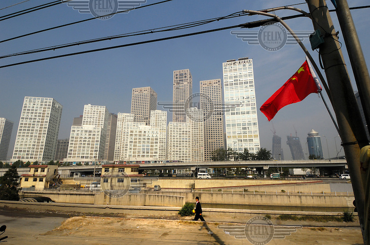 A Chinese flag flies in front of Central Business District Chaoyang skyscrapers, with Jianwai SOHO at centre.