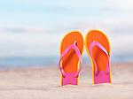 Close up of a pair of colorful orange flip flops in sand at the beach under blue sky background