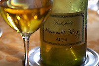 A half empty dusty old bottle with a hand written label saying Louis Jadot Meursault Blagny 1978 white burgundy and a glass of wine on a dining table, Maison Louis Jadot, Beaune Côte Cote d Or Bourgogne Burgundy Burgundian France French Europe European
