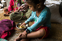 Aastha Baniya (6) eats lunch as she sits with her grandmother in their temporary home in Chautara, Sindhupalchowk, Nepal on 29 June 2015. The three girls lost their mother during the April 25th earthquake that completely levelled their house. Aastha was buried under the rubble together with her mother but Aastha survived. As their father Ratna Baniya (28) cannot care for the children on his own, SOS Childrens Villages has since been supporting the grandmother with financial and social support so that she can manage to raise the children comfortably and ensure that they will all be schooled. Photo by Suzanne Lee for SOS Children's Villages