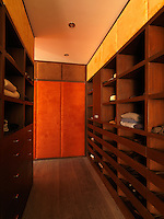 The walls of this bespoke walk-in wardrobe are lined with shelves and drawers