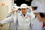 Carlos Ghosn, president and CEO of Nissan Motor Co., is given a hand putting on a jacket at the automaker's engine assembly plant in Yokohama, Japan on Monday 26 Oct.  2009. .Photographer: Robert Gilhooly/Bloomberg News