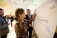 """TALLAHASSEE, FLA. 5/3/13-SESSIONEND050313CH-Hedy Weddington of Auburndale, center, a lobbyist with Florida Strategic Group, signs a giant get well card held by Van Poole, right, for long-time lobbyist and former Sen. Ken Plante during the final day of the legislative session May 3, 2013 at the Capitol in Tallahassee. """"If anybody wanted to know how you define statesman I would say  Ken Plante,"""" Weddington said..COLIN HACKLEY PHOTO"""