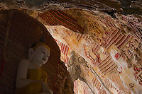 The historical and amazing natural limestone Kaw-goon Cave near the village of Kaw -goon. The cave is decorated with thousands of terra-cottta votive tablets on its interior stone walls. The cultural heritage  of the arts related to the late Bagan Period, 13th Century. And Ink and stone inscriptions from the Mon. Hpa An, Myanmar, Burma.