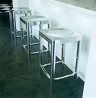 Detail of three chrome stools on the tiled floor of the kitchen
