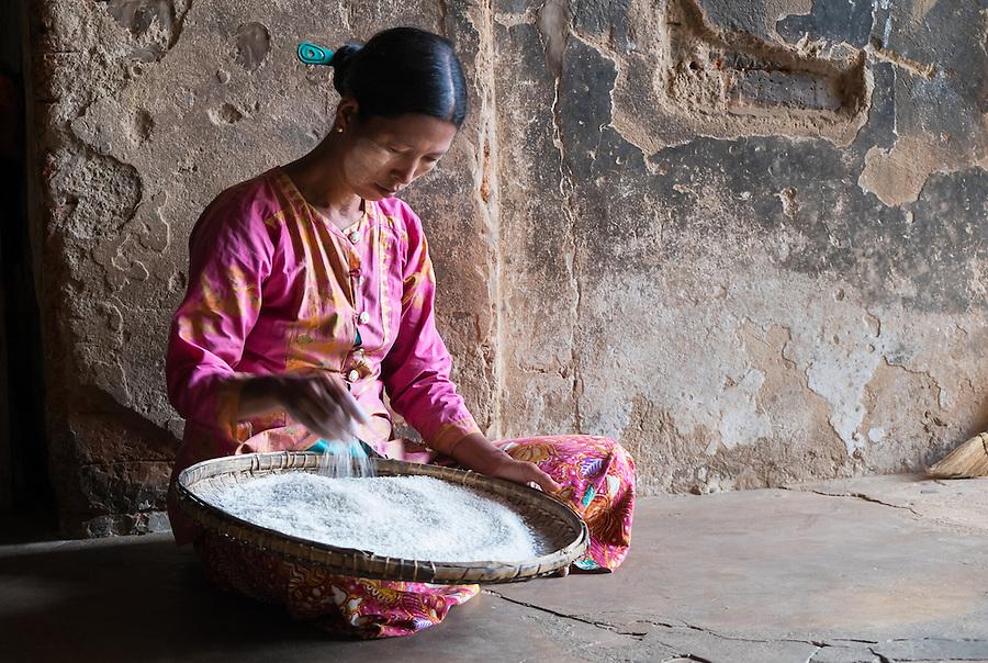 BAGAN, MYANMAR - CIRCA DECEMBER 2013: Burmese woman with a bowl full or rice