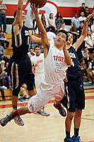 Troy's Ryan Murase, center, goes airborne while attempting a shot under his team's basket on Friday against Sonora.