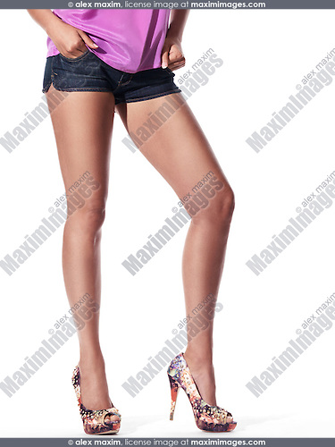 Closeup of sexy legs of young woman wearing denim shorts and high heel shoes isolated on white background