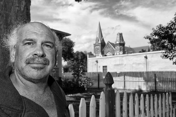 A Bald Man standing next to a white picket fence with a large stone church in the back ground