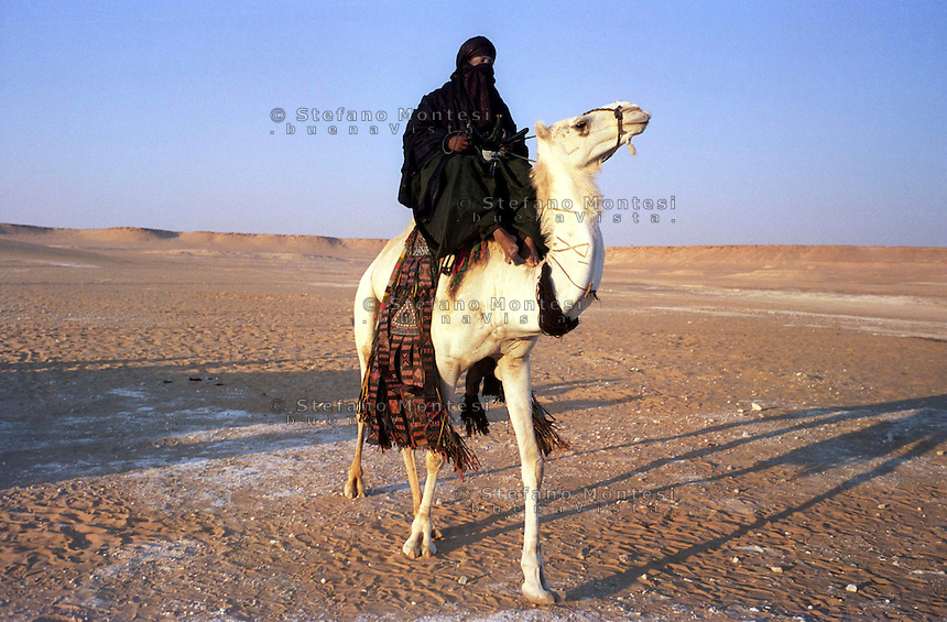 Libia, Ghadhames 2002.Tuareg  sul cammello nel deserto del Sahara.Libya, Ghadhames 2002.Tuareg on the camel in the desert of the Sahara.