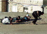 Photographers take cover and photograph as Palestinian youths throw stones at Israeli soldiers on the outskirts of Ramallah.
