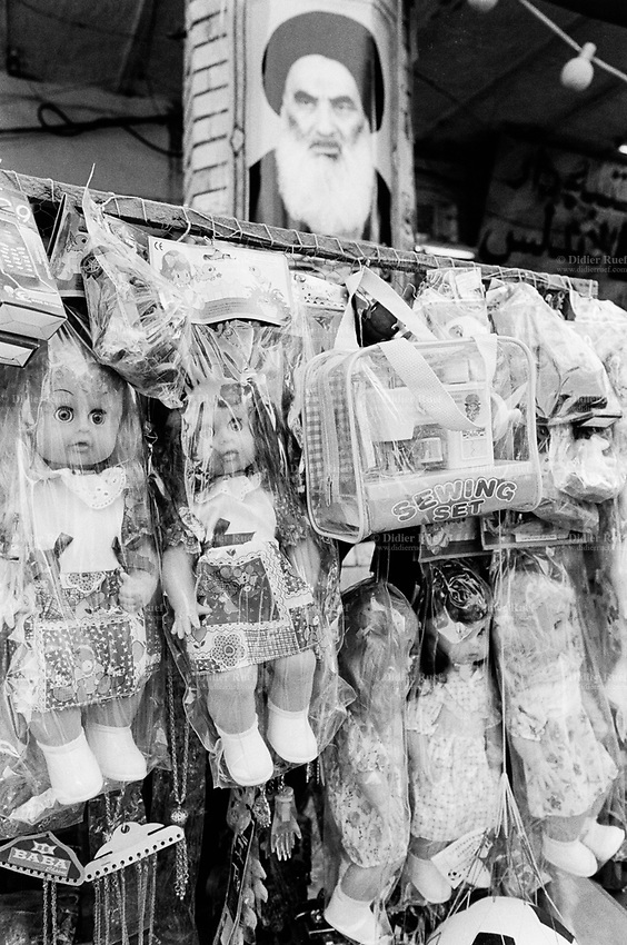 Iraq. Najaf. Dolls for girls sold in the street. A picture of the shiite spritual and Grand Ayatollah Sayyid Ali al-Husayni al-Sistani is taped on the wall. Grand Ayatollah Sayyid Ali al-Husayni al-Sistani is the  highest-ranking Twelver Shia marja in Iraq and the leader of the Hawza of Najaf. Marja is the label provided to Shia authority, a Grand Ayatollah with the authority to make legal decisions within the confines of Islamic law for followers and less-credentialed clerics. After the koran and the Prophets and Imams, marjas are the highest authority on religious laws in Shia Islam. 26.02.04 © 2004 Didier Ruef ..