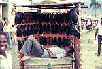 Shoeless boy asleep on his stall. Images of the capital,Port au Prince, Haiti 1975