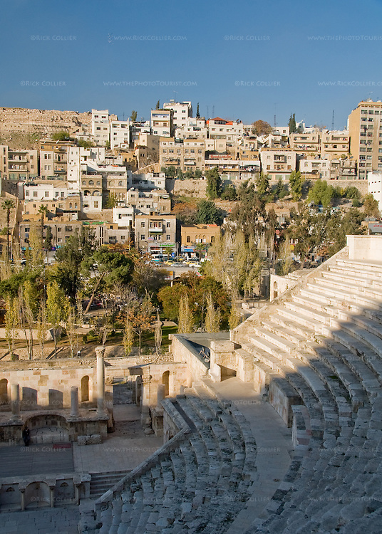 Apartment buildings rise on the hills around the Ancient Roman amphitheater in the center of old Amman, Jordan.  Like Rome itself, Amman is built on seven hills.  This was a prominent provincial capital named Philadelphia under the rule of Ancient Rome.  © Rick Collier