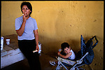 At the bartering market in Quilmes a mother smokes a cigerette while her child looks elsewhere.