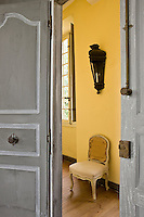Grey-painted double doors open from a bedroom into the yellow hallway