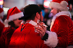A woman dressed as Santa Claus holds up a shot of alcohol while she takes part at the Santacon's Annual Festival at Times Square in New York, United States. 14/12/2012. Photo by ZAMEK