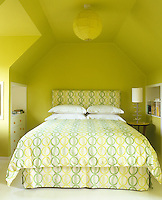 Acid yellow attic bedroom with small double bed