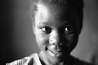 Portrait of a young girl.  This young girl, although still has her father, has lost her mother and many of her aunts and uncles to HIV/AIDS.  Mbiko, Mokono District, Uganda, Africa. June 2004 © Stephen Blake Farrington.