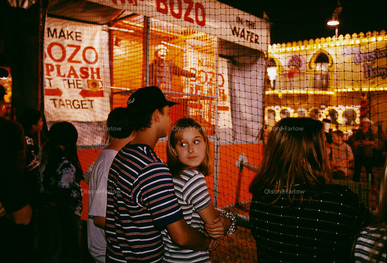 """Midway entertainment captivates even multi-media-jaded teenagers. Boys and girls at the Brazoria County Fair in Texas enjoy a little romance, a little comedy, and a little playful revenge as """"bozo"""" the clown strafes the crowd with jocular insults."""