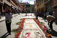 People decorate a procession route with flowers and rugs depicting religious motifs during Holy Week in Ayacucho, Peru.
