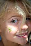 Africa, Kenya. Praying Mantis on young girls face. MR