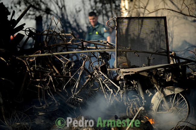 Bicycles and motorcycles burnt are seen in San Agustin de Guadalix during a forest fire near Madrid, on August 11, 2012. Wildfires raged Saturday in Spain's Canary Islands and in mainland Galicia, as hundreds fought a blaze near Mount Athos in Greece, a UN Heritage Site housing the world's oldest monastic community. (c) Pedro ARMESTRE