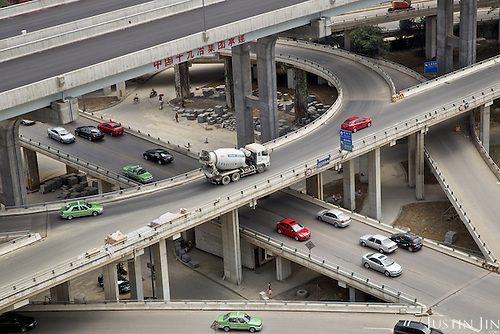 Cars pass through a busy inter junction -- beneath a &quot;super ring&quot; that was still under construction -- in one of the fastest-urbanizing cities in China.<br /> <br /> Situated in southwestern China, away from the coast, this city is the engine of China's inland economic development. <br /> <br /> China is pushing ahead with a dramatic, history-making plan to move 100 million rural residents into towns and cities between 2014 and 2020 &mdash; but without a clear idea of how to pay for the gargantuan undertaking or whether the farmers involved want to move.<br /> <br /> Moving farmers to urban areas is touted as a way of changing China&rsquo;s economic structure, with growth based on domestic demand for products instead of exporting them. In theory, new urbanites mean vast new opportunities for construction firms, public transportation, utilities and appliance makers, and a break from the cycle of farmers consuming only what they produce.<br /> <br /> Urbanization has already proven to be one of the most wrenching changes in China&rsquo;s 35 years of economic reforms. Land disputes rising from urbanization account for tens of thousands of protests each year.