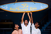 "(Left to right) Satyaraj, Daruka and Dicky are seen with the surfboard with the pun on the title, Home Sweet Home in the their own verison of Om Sweet Om at the Kaliya Mardana Krishna Ashram in the coastal town of Mulki, just north of Mangalore, Karnataka, India.  ..Krishna devotees in the Gaudiya Vaishnava tradition of Hinduism, they are known collectively as the ""surfing swamis."" The ""surfing ashram"" is growing in popularity and surfing here is a form of meditation, a spiritual practice leading to heightened states of awareness."