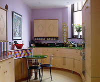 A kitchen with purple walls has bespoke blond wood units with green work surfaces built in a smooth curve.