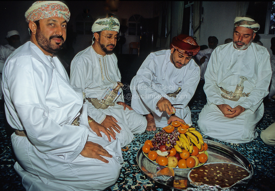 Mudayrib, Oman, Arabian Peninsula, Middle East - Omani Men Taking Breakfast before  Prayers on the Eid al-Adha (Feast of the Sacrifice), the annual feast through which Muslims commemorate God's mercy in allowing Abraham to sacrifice a ram instead of his son, to prove his faith.  The white dishdasha, multicolored msarr or massar (headdress), and curved silver khanjar (dagger) make up their attire.  A plate of halwa with almonds accompanies the fruit.