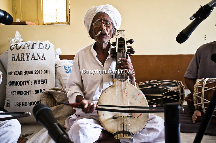 75-year-old Manganiyar artist, Saqar Khan sings and plays his Kamancha (music instrument) during field recordings inside their house in Hamira village of Jaiselmer district in Rajasthan, India. Photo: Sanjit Das/Panos