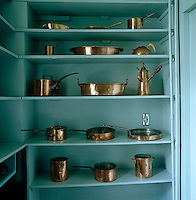 A walk-in cupboard in the kitchen has been painted a bright turquoise with a collection of antique copper pans glowing on the shelves