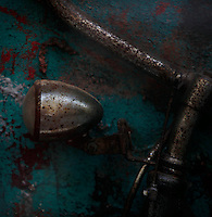 Detail of a rusty bicycle lamp against a differentiated turquoise background in Via Roma in Ortigia, Syracuse, Sicily, pictured on September 14, 2009, in the morning. The 2,700 year old Syracuse is a province and a city in southern Italy on the Island of Sicily. The island Ortigia is the historic centre of Syracuse. Today the city is a UNESCO World Heritage Site. Founded by Ancient Greek Corinthians and allied with Sparta and Corinth, it was a very powerful city-state and one of the major powers of the Mediterranean.  In the 17th century it was heavily destroyed by an earthquake. Many buildings date back to the  19th century when it regained importance. Picture by Manuel Cohen.