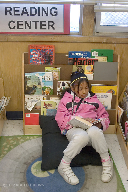 Oakland CA 2nd grader absorbed in book in classroom Reading Center