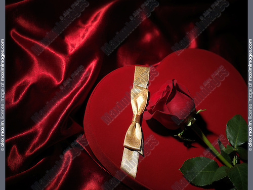 Red heart-shaped gift box and a red rose
