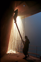 A worker holds a ladder for the welders working above in the ship-breaking yard in Gaddani.