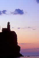 THE SPLIT ROCK LIGHTHOUSE IS SILHOUETTED AT DAWN AT SPLIT ROCK LIGHTHOUSE STATE PARK NEAR TWO HARBORS, MINNESOTA.