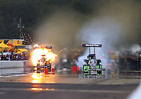Aug 19, 2016; Brainerd, MN, USA; NHRA top fuel driver Chris Karamesines (left) explodes an engine on fire alongside Clay Millican during qualifying for the Lucas Oil Nationals at Brainerd International Raceway. Mandatory Credit: Mark J. Rebilas-USA TODAY Sports