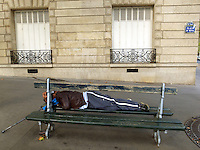 France. Department Ile-de-France. Paris. A gypsy man sleeps on a wood bench on the Place d'Iena in the 16th arrondissement. 14.07.2011 &copy; 2011 Didier Ruef